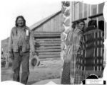 Three Cheyenne women looking in window with Two Moons behind them